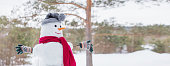snowman in red scarf in forest