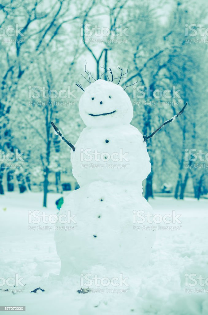 snowman in winter time in park full of snow stock photo