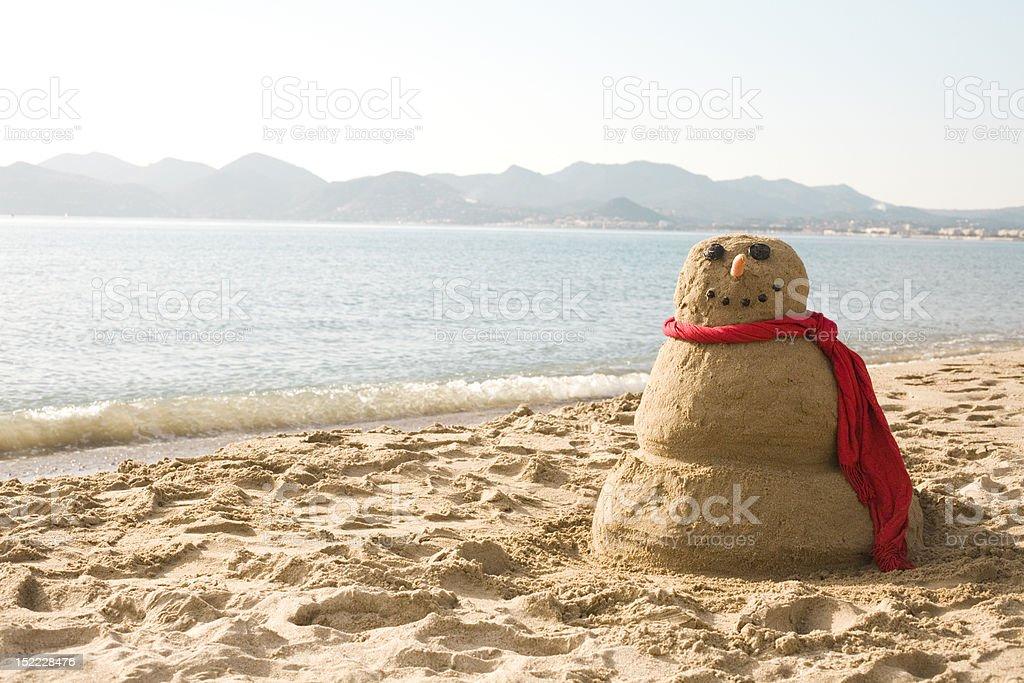 A snowman made from sand on a beach near the sea stock photo