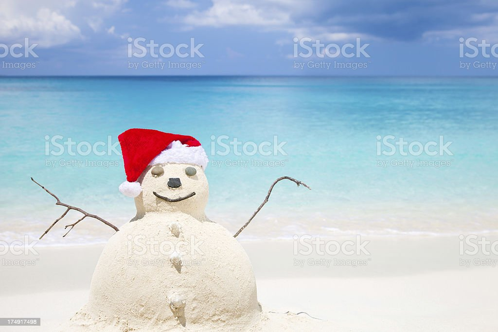 Snowman made of sand in Santa Claus hat at beach stock photo