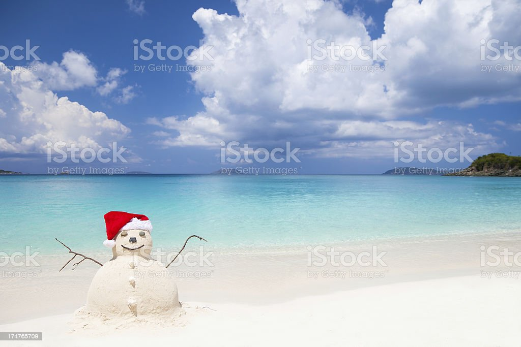 Snowman made of sand in Santa hat at a beach stock photo
