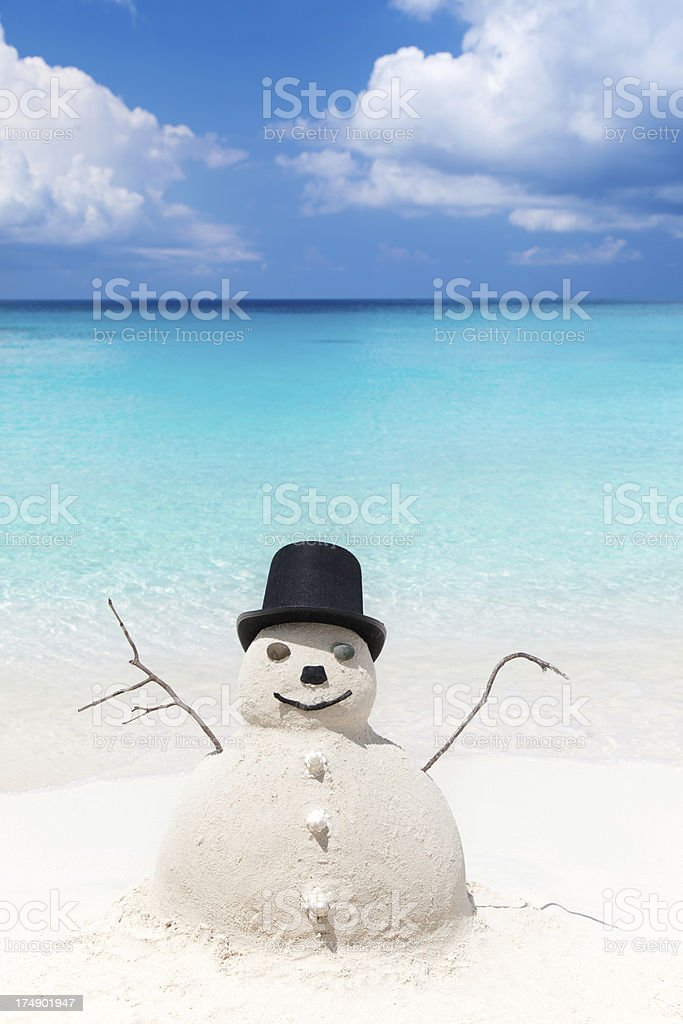 Snowman made of sand in top hat at a beach royalty-free stock photo