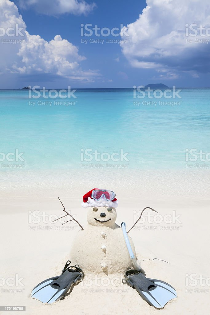 Snowman made of sand with snorkeling gear at a beach stock photo