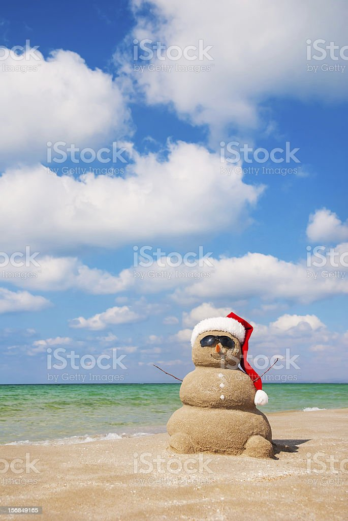 Snowman made out of sand on a beach by the ocean stock photo