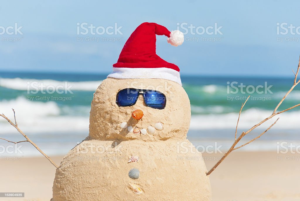 Snowman Made Out Of Sand With Santa Hat stock photo