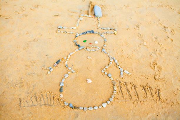 schneemann der felsen im sand am strand - bemalte muscheln stock-fotos und bilder