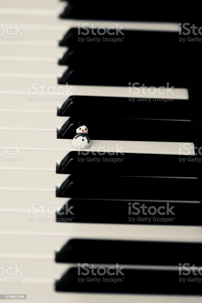 Snowman on a piano playing christmas music stock photo