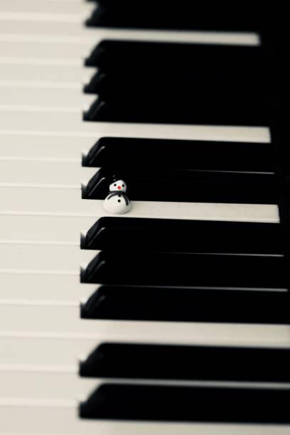 bonhomme de neige sur un piano à jouer de la musique de noël - josianne toubeix photos et images de collection