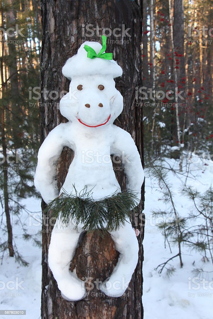 Snowman on a pine  in the form of a monkey stock photo