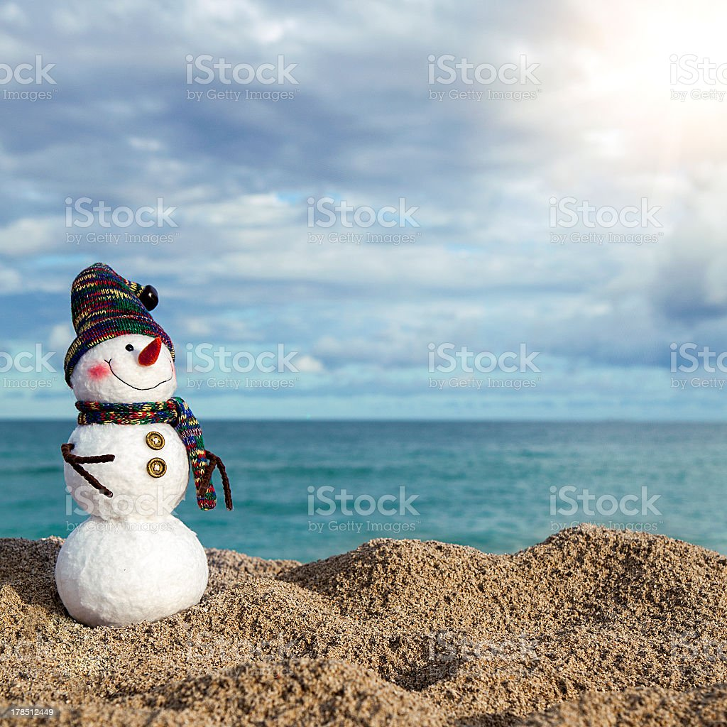 Snowman on a sunny beach who is not yet melting stock photo