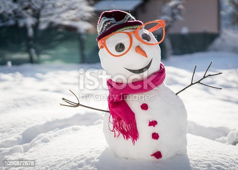 istock Snowman on snow background 1056877678