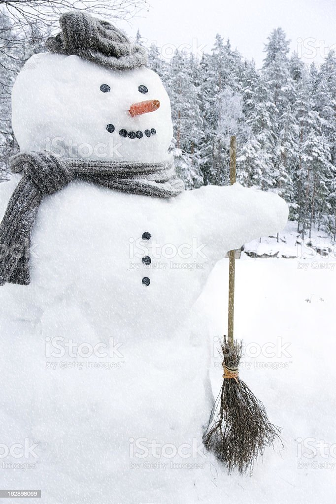 Snowman outside in snowfall royalty-free stock photo