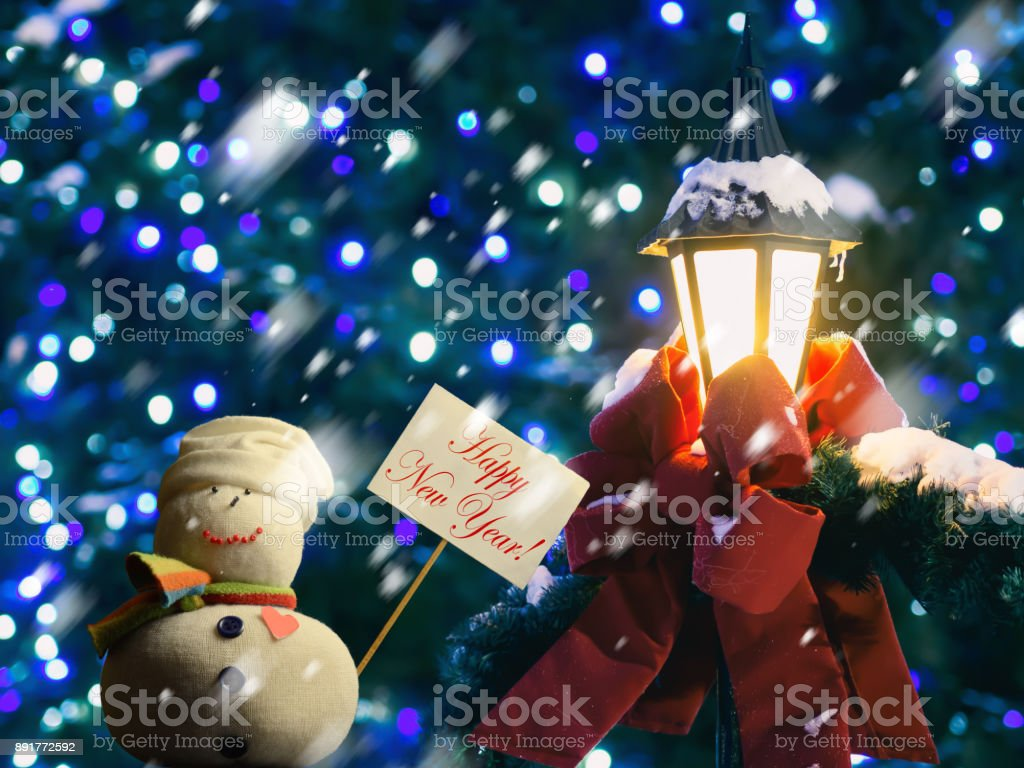 "Snowman, placard with text ""Happy New Year!"", street lantern, ribbon. stock photo"