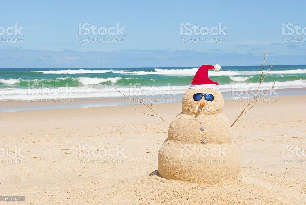 Snowman resists melting process on beach stock photo