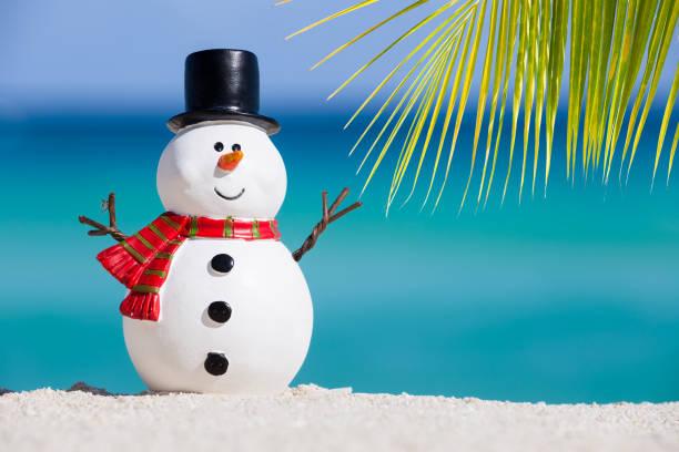 Snowman toy at white sandy beach stock photo