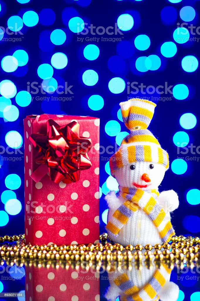 Snowman toy, gift in package and golden beads on a glass table with a beautiful blue bokeh stock photo