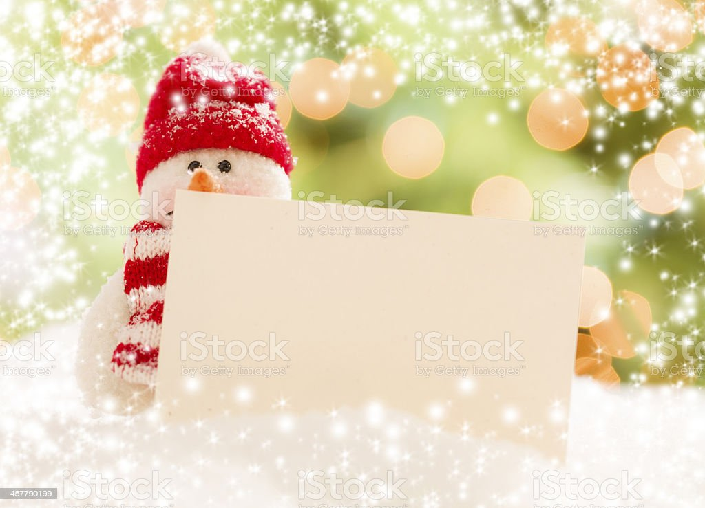 Snowman with blank white card and lights royalty-free stock photo