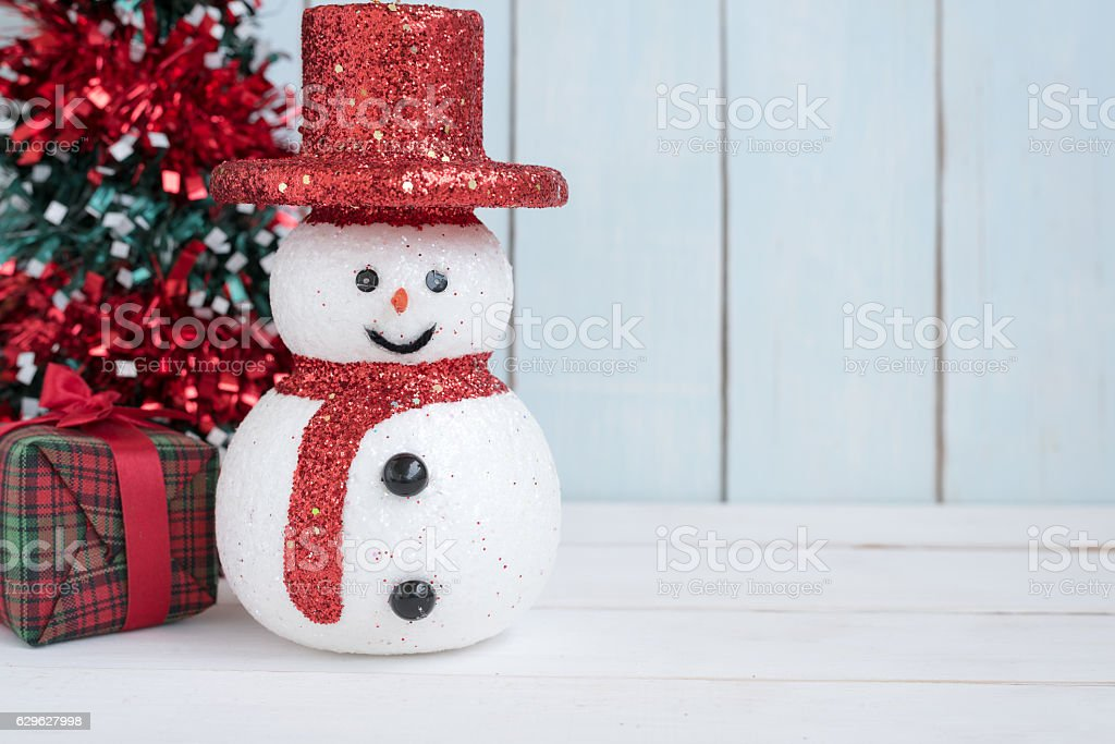 Snowman with gift box and christmas tree stock photo
