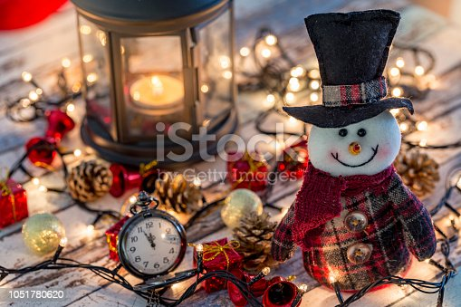 istock Snowman with pocket watch, christmas decorations and lights 1051780620