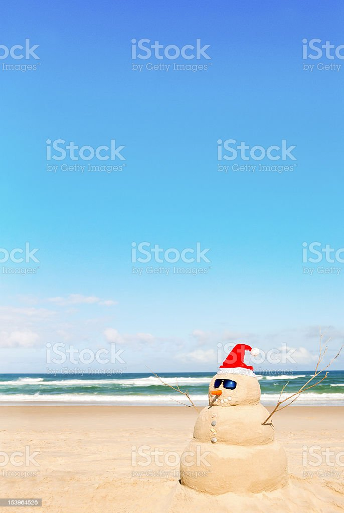Snowman with Santa hat and sunglasses with sand on the beach stock photo