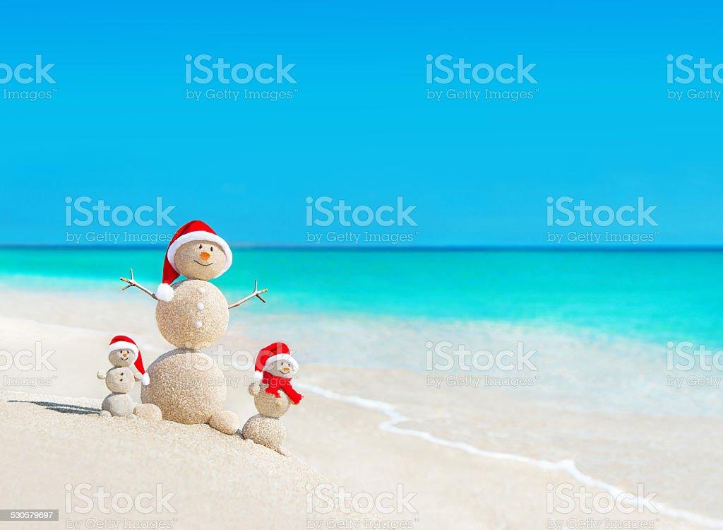 Snowmen family at beach in santa hats.Christmas concept stock photo