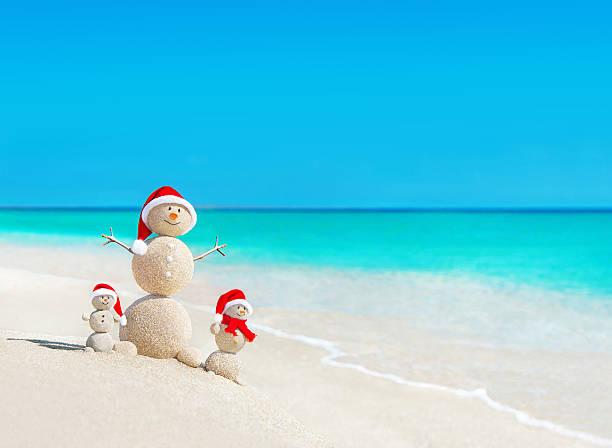 snowmen family at beach in santa hatschristmas concept stock photo