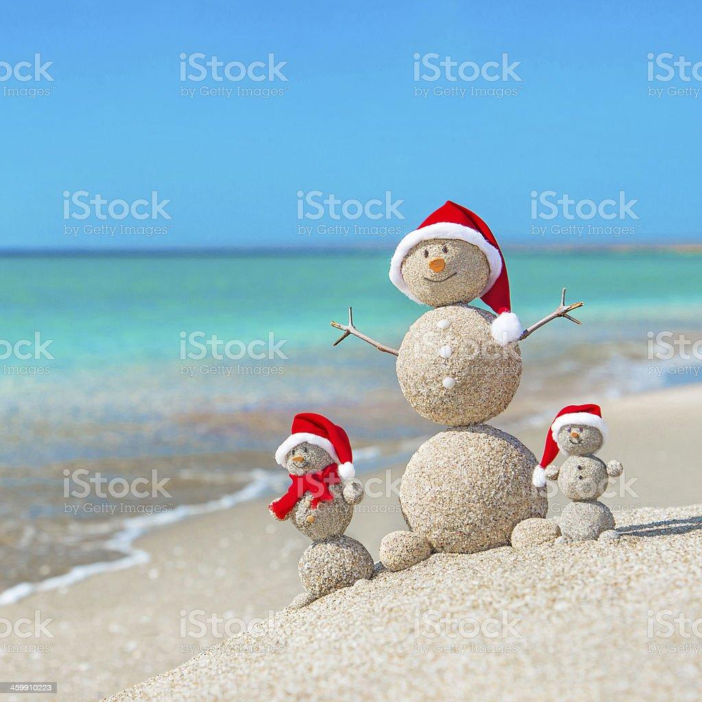 Snowmen family at sea beach in christmas santa hat. stock photo
