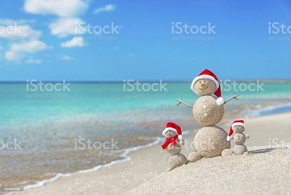 Snowmen family at sea beach in santa hat. Christmas concept. stock photo