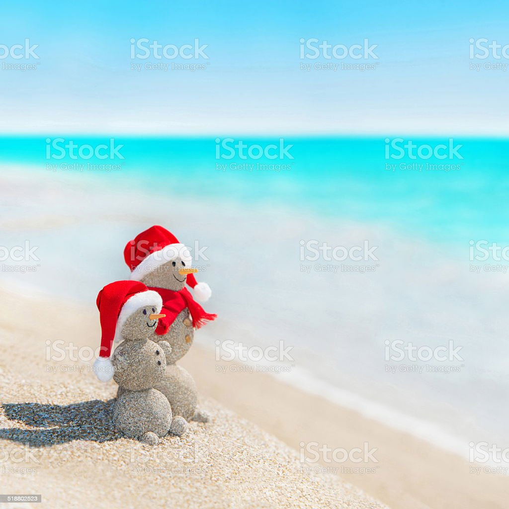 Snowmen friends at beach in christmas hat. New years holiday stock photo