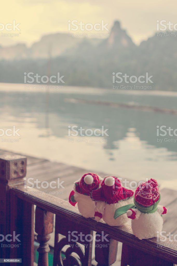 Snowmen looking out to sea. Christmas decorations. Vacation stock photo