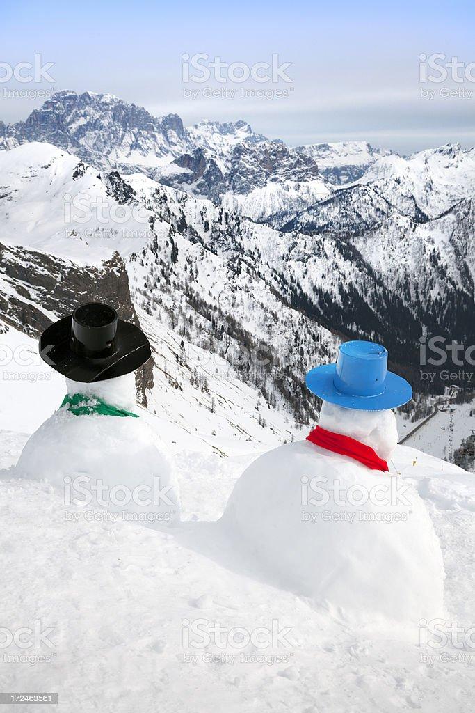 Snowmen surveying the mountains royalty-free stock photo