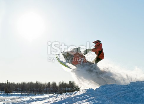 Snowmobile driver jumping spectacular over snow hill in winter landscape