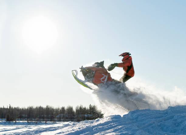 Motorroller Fahrer springen spektakulär über Schneehügel in Winterlandschaft – Foto