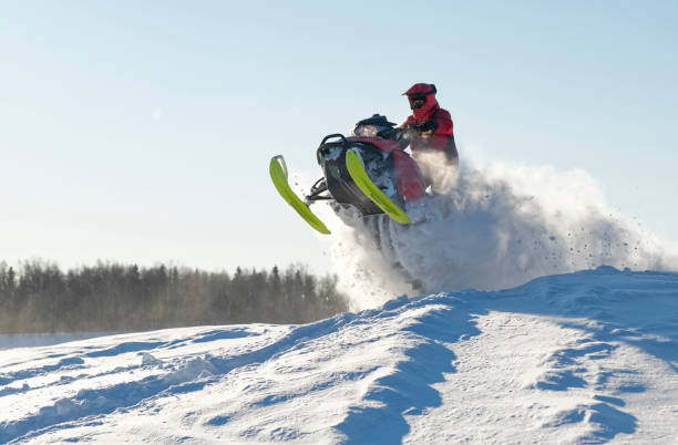 Snowmobile driver jumping spectacular over snow hill in winter landscape stock photo