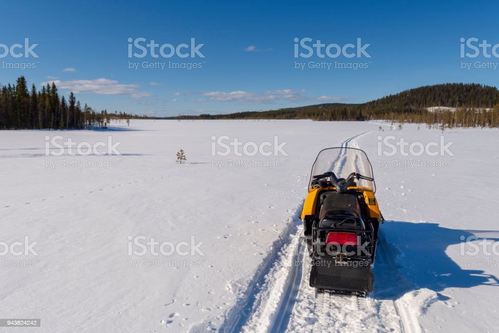 Snowmobile on a track on a frozen morass with a mountain and a blue stock photo
