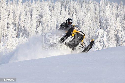 Snowmobiler busting through a drift and jumping