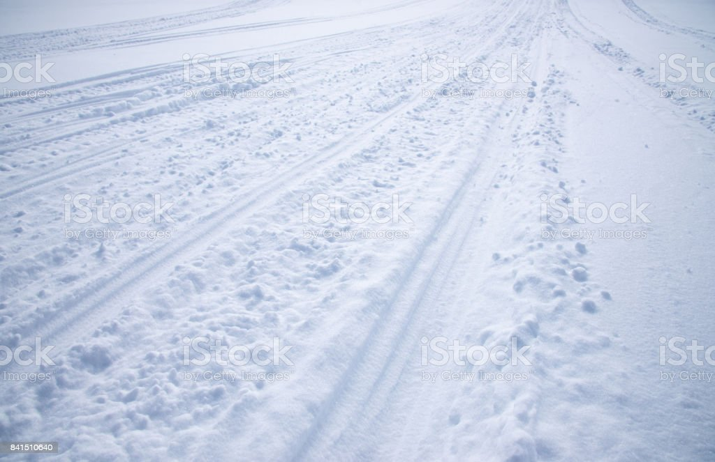 Snowmobile Tracks In Snow Mountains As Background Winter Season