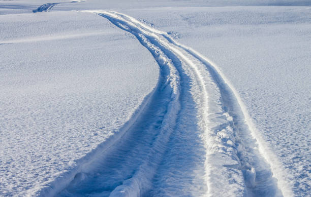 Snowmobile trail in the snow Snowmobile trail in the snow in spring wasser photos stock pictures, royalty-free photos & images