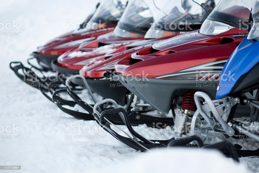 Snowmobiles in a row stock photo