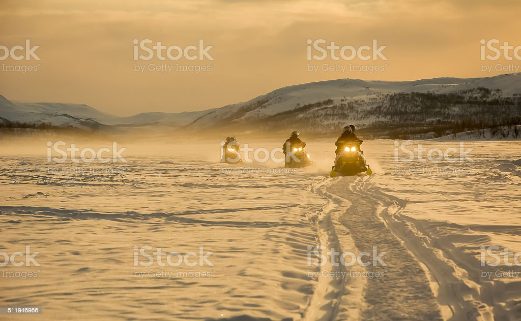 Snowmobiles in sunset stock photo
