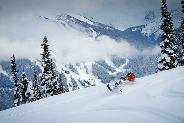 Snowmobiling on the top of the snowy mountain stock photo