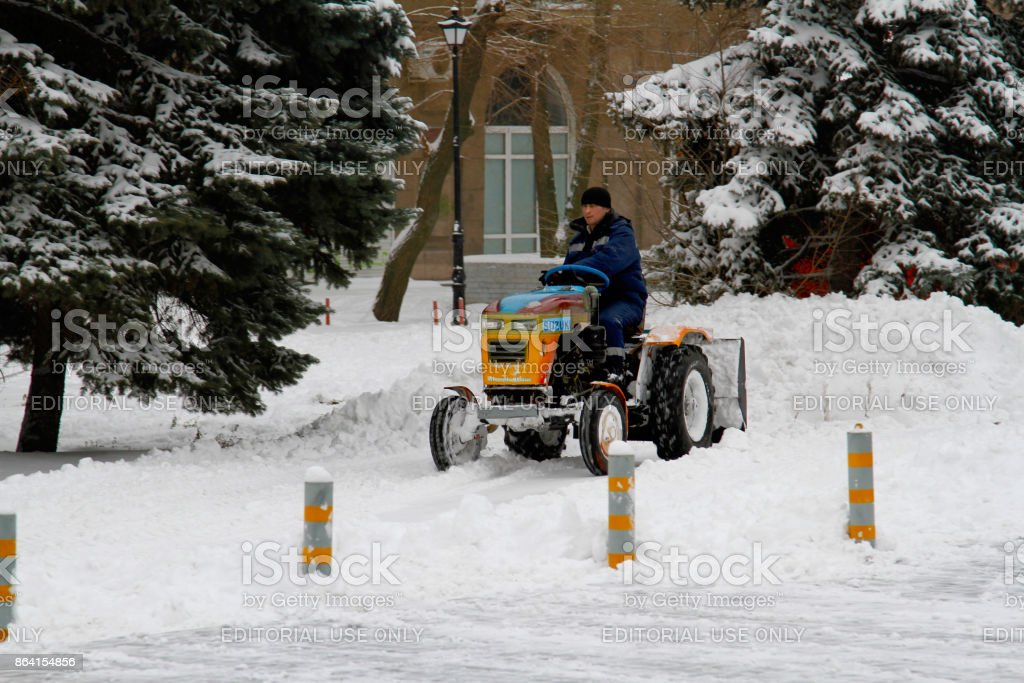 Snowplow cleans from the road snow in Volgograd stock photo