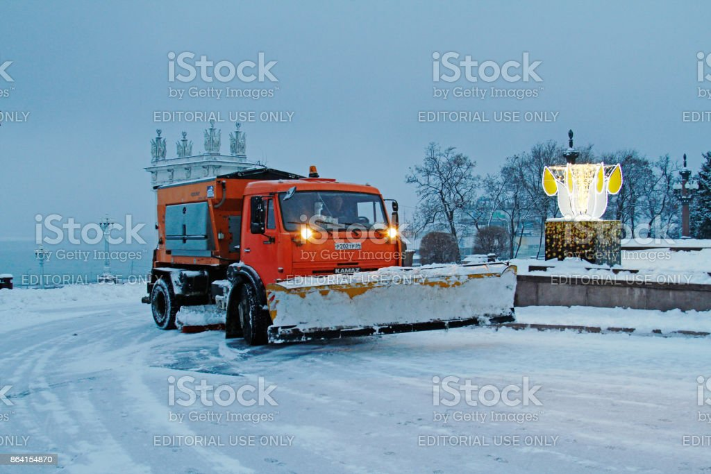 Snowplow cleans from the road snow on the Central embankment of the Volga river in Volgograd royalty-free stock photo