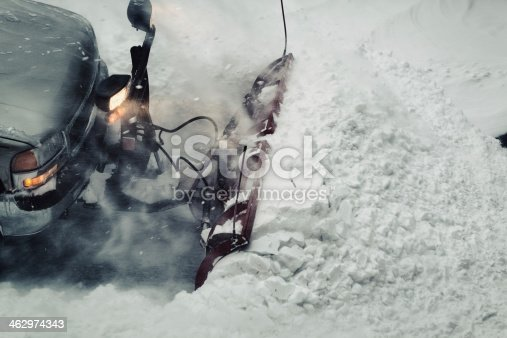 A snowplow operator clears a large snowfall from a parking lot.