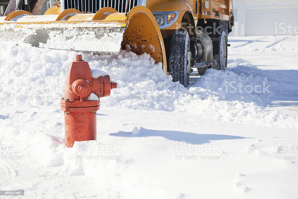 Snowplow Plowing Snow from City Street near Fire Hydrant stock photo