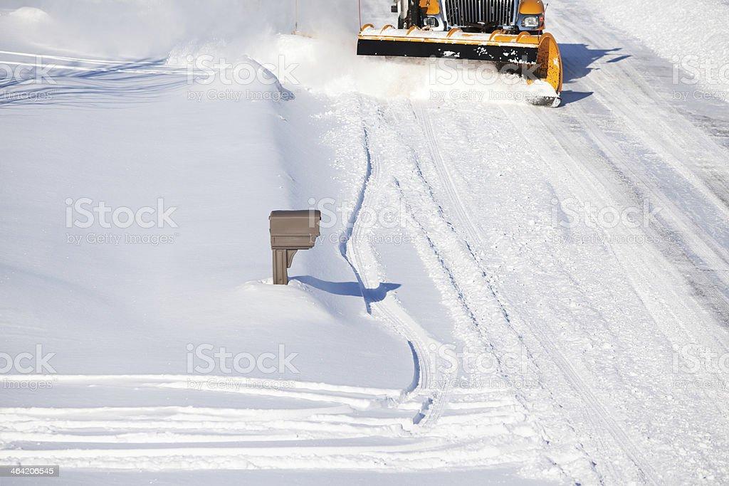 Snowplow Plowing Snow from City Street near Mailbox stock photo