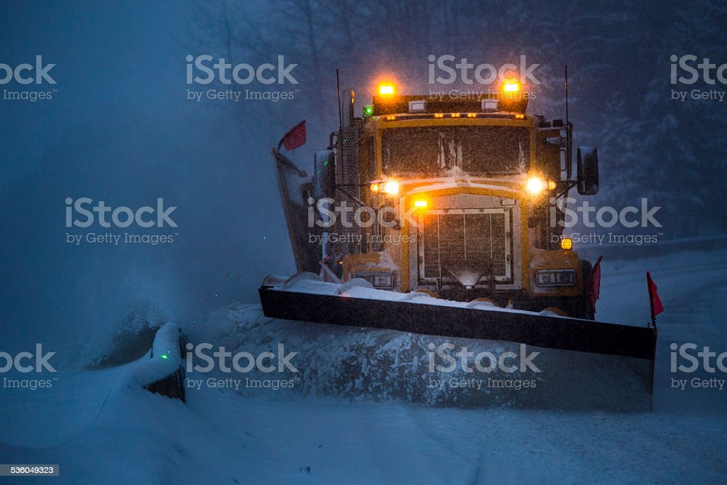 Snowplow plowing the highway during snow storm. stock photo