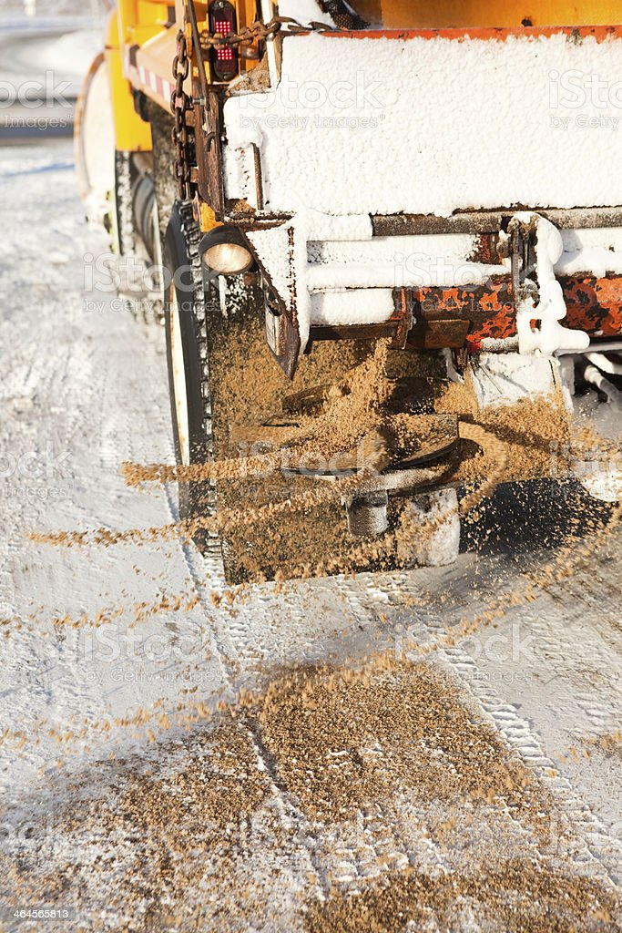Snowplow Spreading Sand on Winter Snow Covered Road stock photo