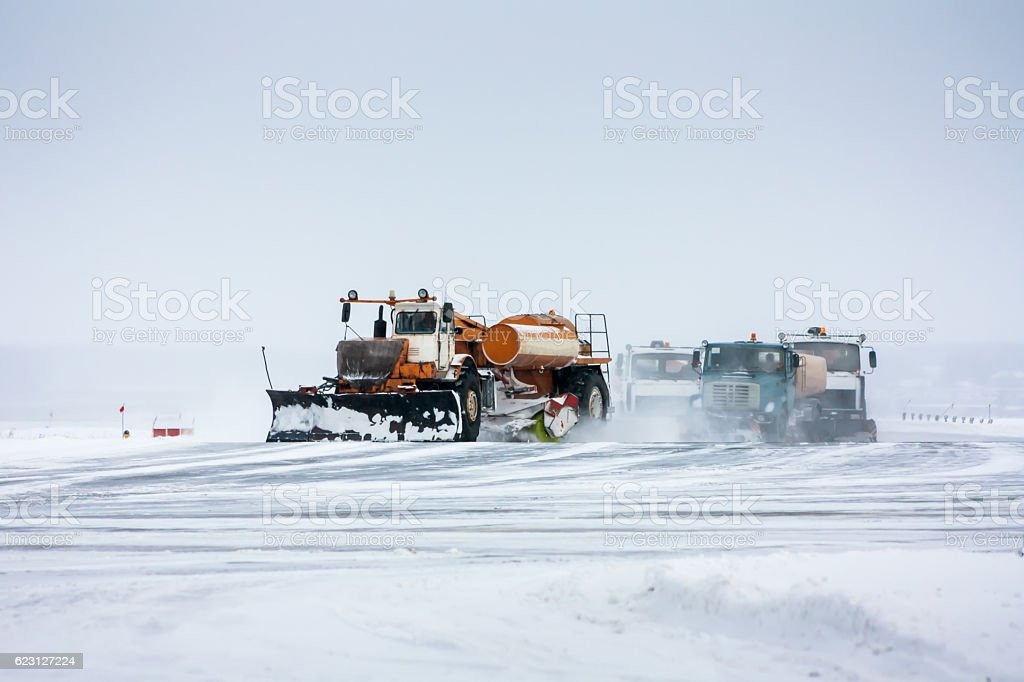Snowplows cleans the runway stock photo