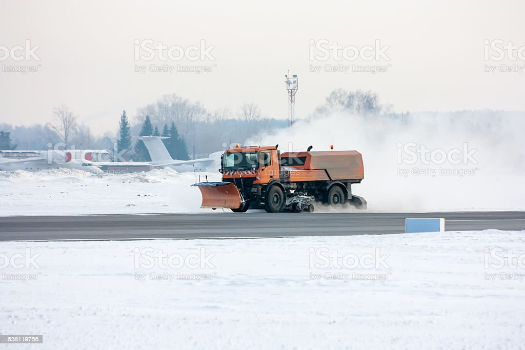 Snow-removal machine cleans the main taxiway at the airport стоковое фото